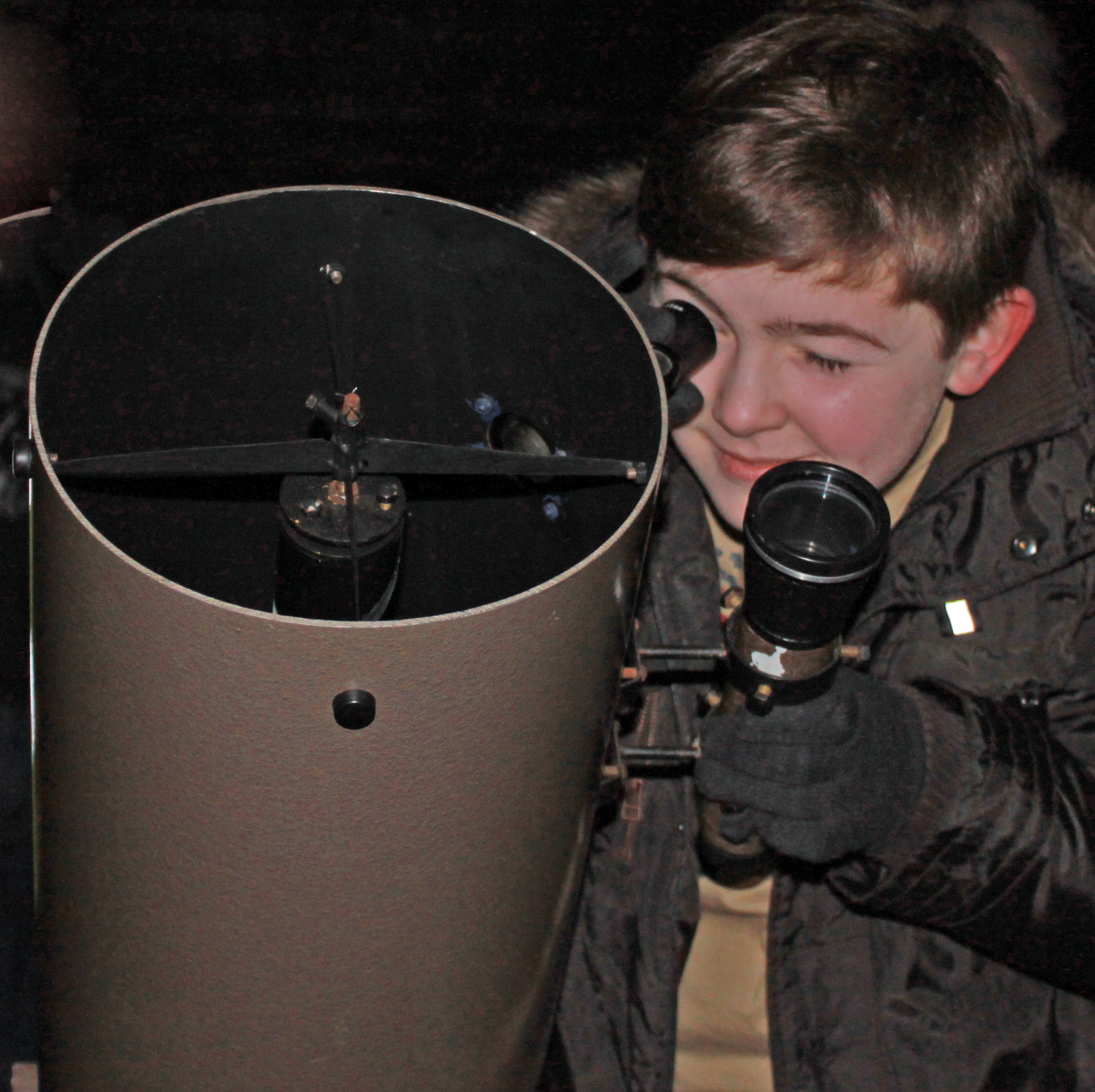 A Young Astronomer looks at the night sky through a telescope